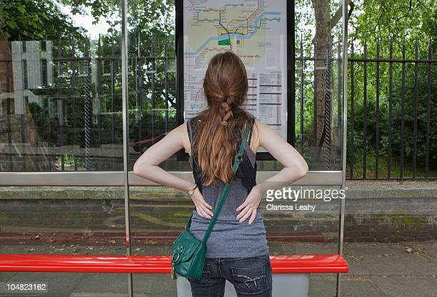 Woman looking at bus time table