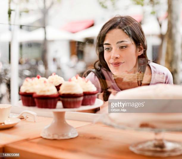 woman looking at cake display in window - hongerig stockfoto's en -beelden