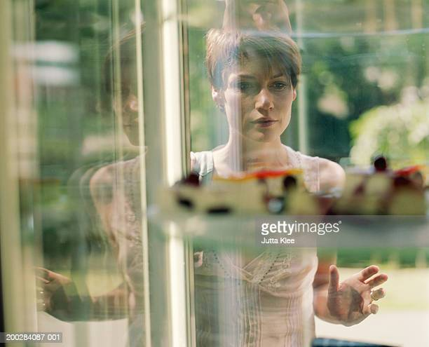 Woman looking at cake display in window, view through glass