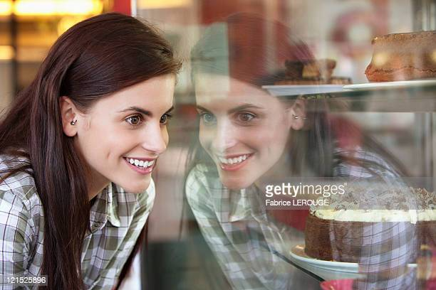 Woman looking at cakes in a bakery window