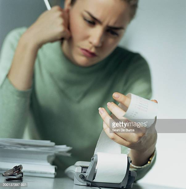 woman looking at calculator tape in office (focus on hand) - addierrolle stock-fotos und bilder