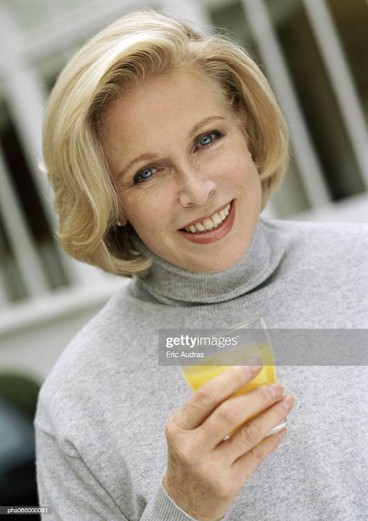 Woman looking at camera holding glass of orange juice, close up, portrait. : Stockfoto