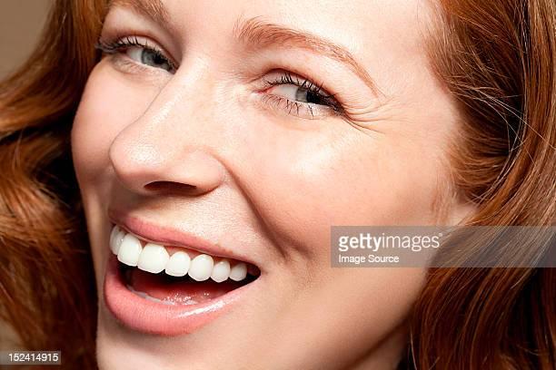 Woman looking at camera laughing, close up