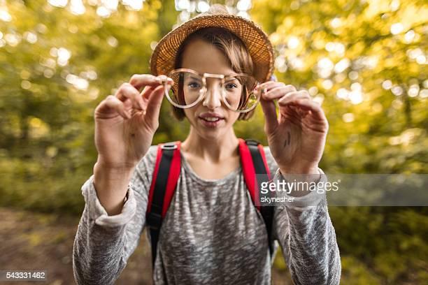 Woman looking at camera through eyeglasses outdoors.