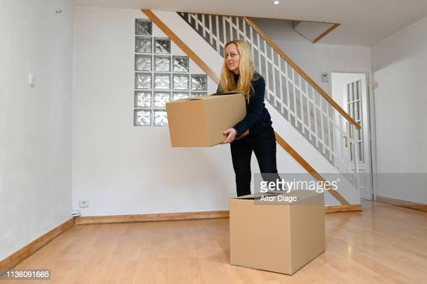 woman looking at camera with a cardboard box in her new house. moving - último cuarto deportes fotografías e imágenes de stock
