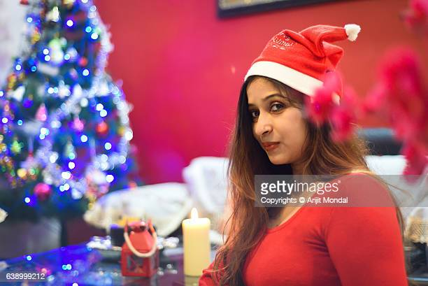 Woman Looking at Camera with Red Dress and Christmas Tree