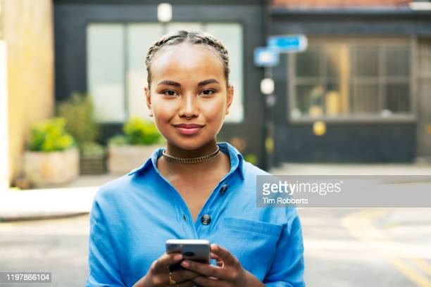 woman looking at camera with smart phone - person in education stock pictures, royalty-free photos & images