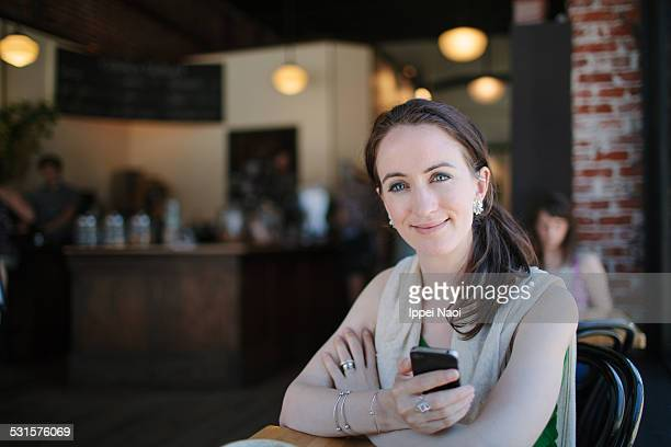 woman looking at camera with smartphone in hand - ippei naoi stock photos and pictures