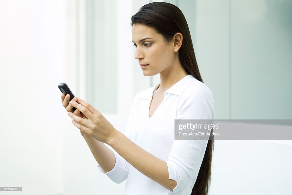 Woman looking at cell phone, side view : Stock Photo