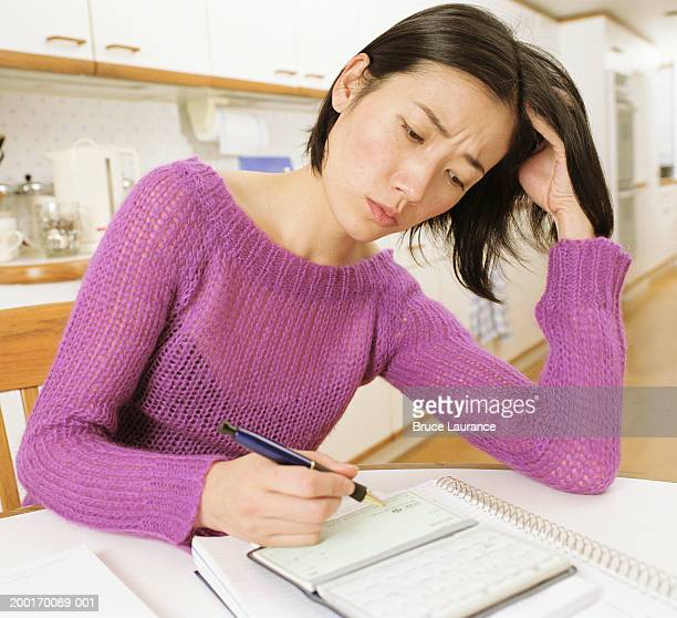 Woman looking at checkbook in kitchen, frowning