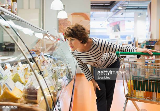 woman looking at cheese counter in supermarket