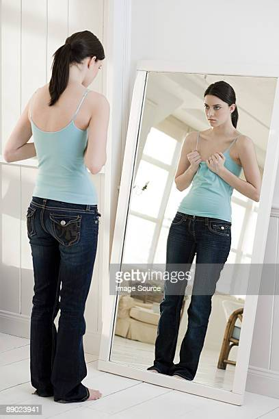 woman looking at chest in mirror - beautiful women breast stock pictures, royalty-free photos & images
