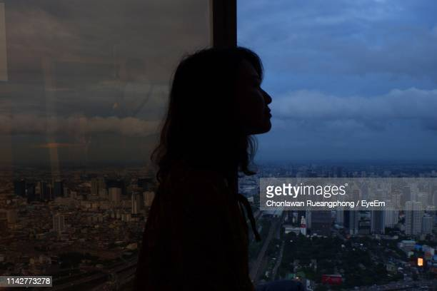Woman Looking At City Buildings Against Sky At Dusk