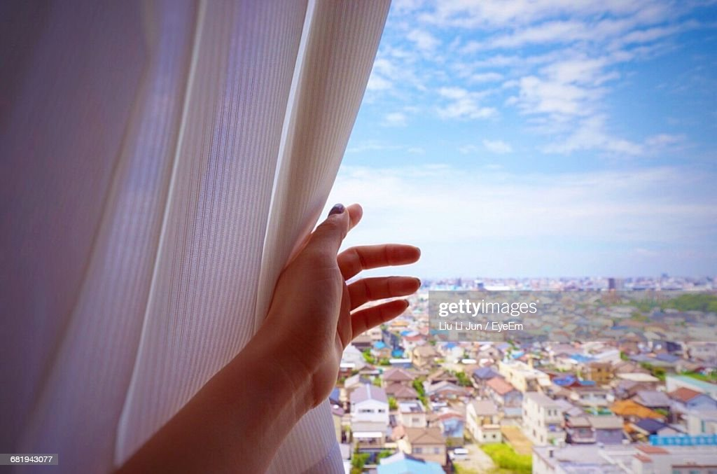 Woman Looking At City View From Window : Stock Photo