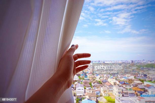 Woman Looking At City View From Window