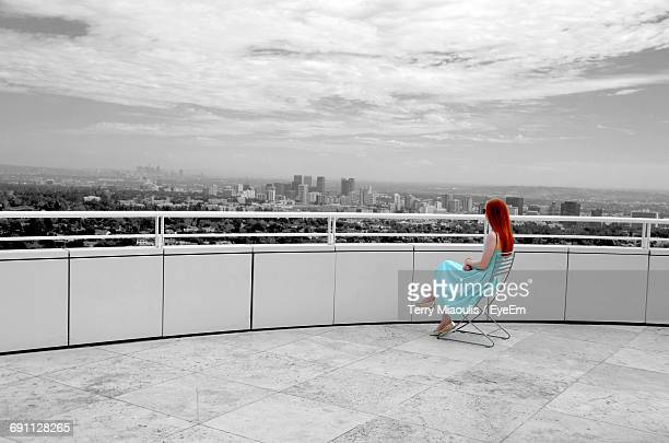 Woman Looking At City While Sitting On Chair In Building Terrace Against Sky