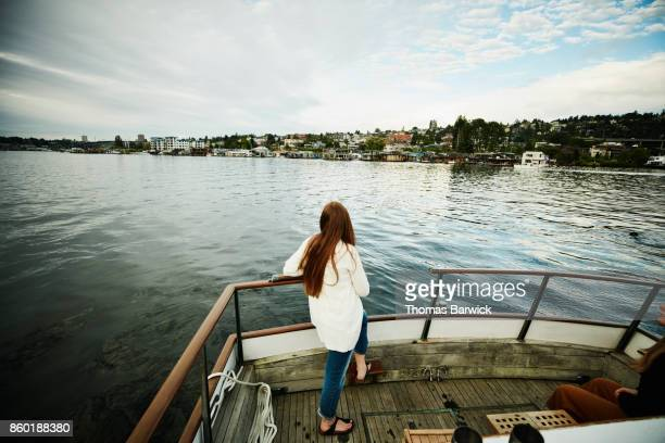 Woman looking at cityscape from stern of boat on summer evening