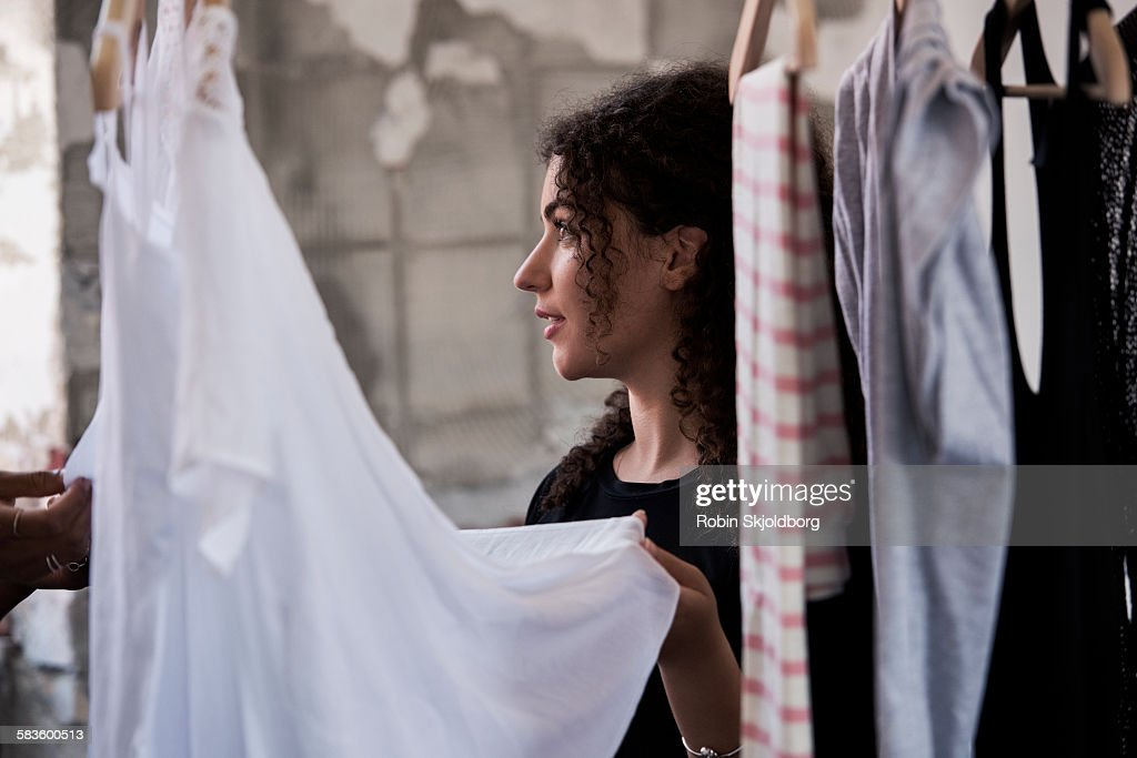 Woman looking at clothes on rack : Stock Photo