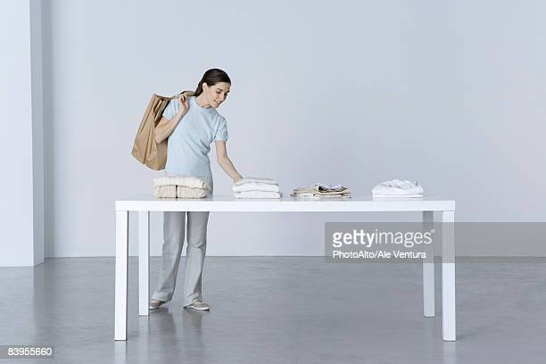 woman looking at clothing folded on table, shopping bags slung over her shoulder - medium group of objects stock pictures, royalty-free photos & images