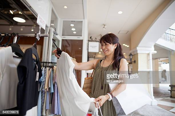 Woman looking at clothing in a shopping mall.