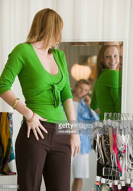 Woman Looking at Clothing in Store Mirror
