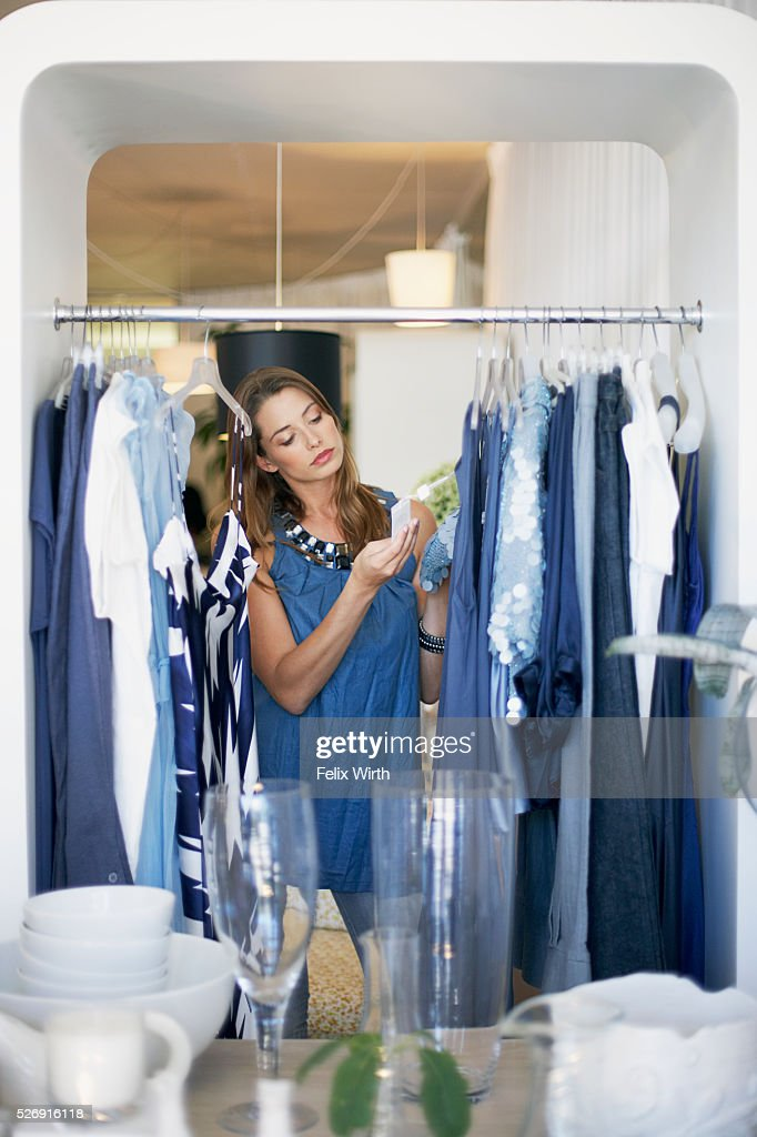 Woman looking at clothing on rack : Stock-Foto