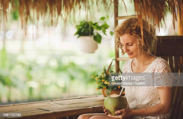 Woman Looking At Coconut While Sitting In Hut