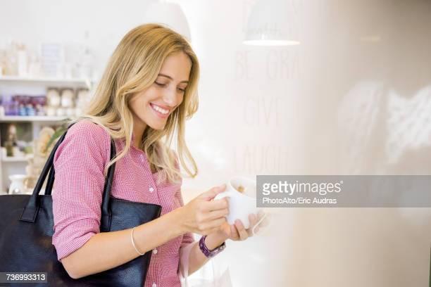 Woman looking at coffee mug in shop