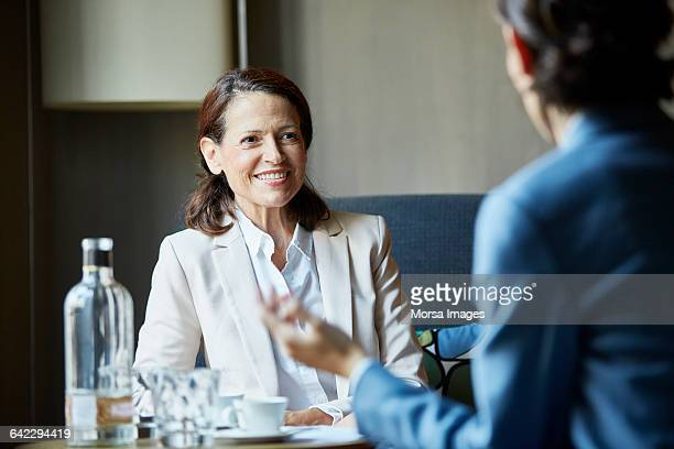 Woman looking at colleague meeting at hotel room