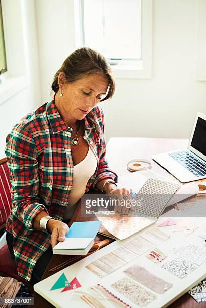 A woman looking at colour and design and collage of patterns. Laptop on desk.