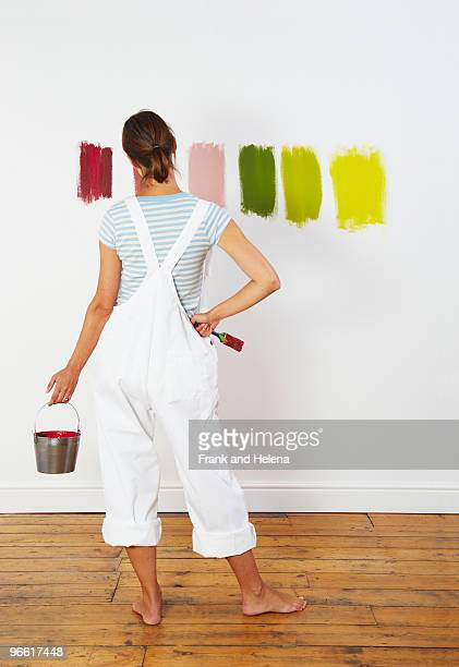 woman looking at colour swatches on wall - main sur la hanche photos et images de collection