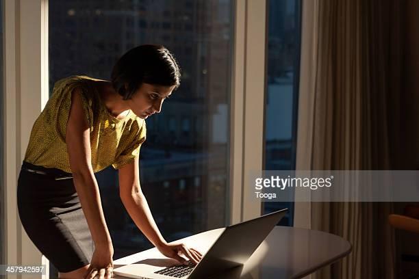 Woman looking at computer late at night