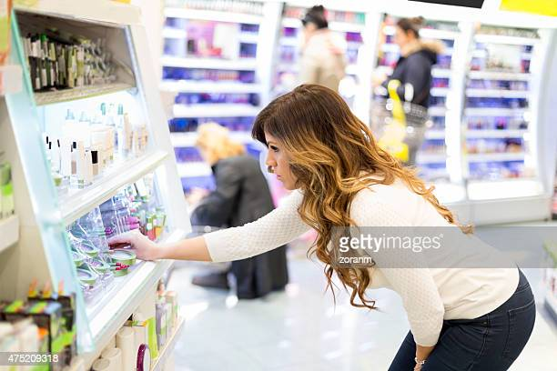 Woman looking at cosmetics in drugstore