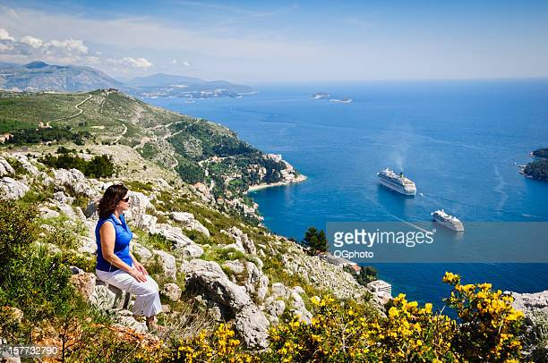 Woman looking at cruise ships in Dubrovnik bay
