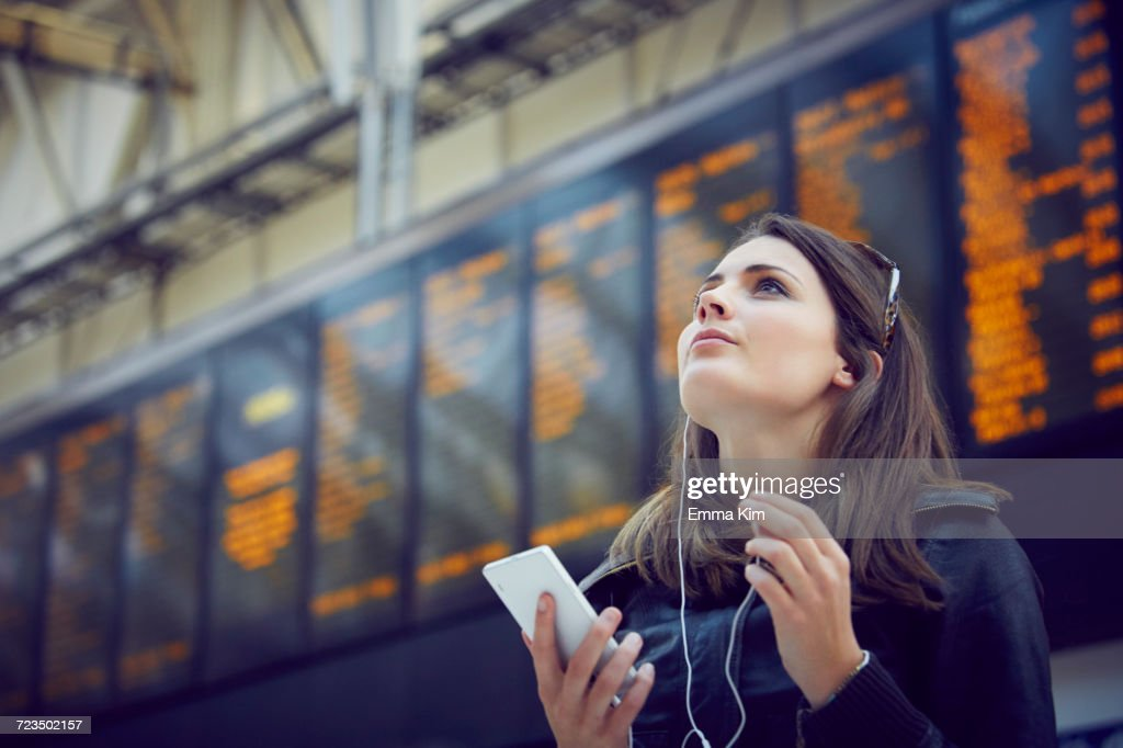 Woman looking at departure information, London, UK : Stock-Foto