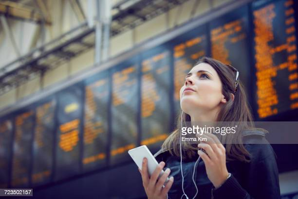 Woman looking at departure information, London, UK