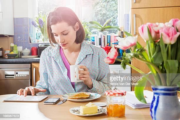 Woman looking at digital tablet while having breakfast.