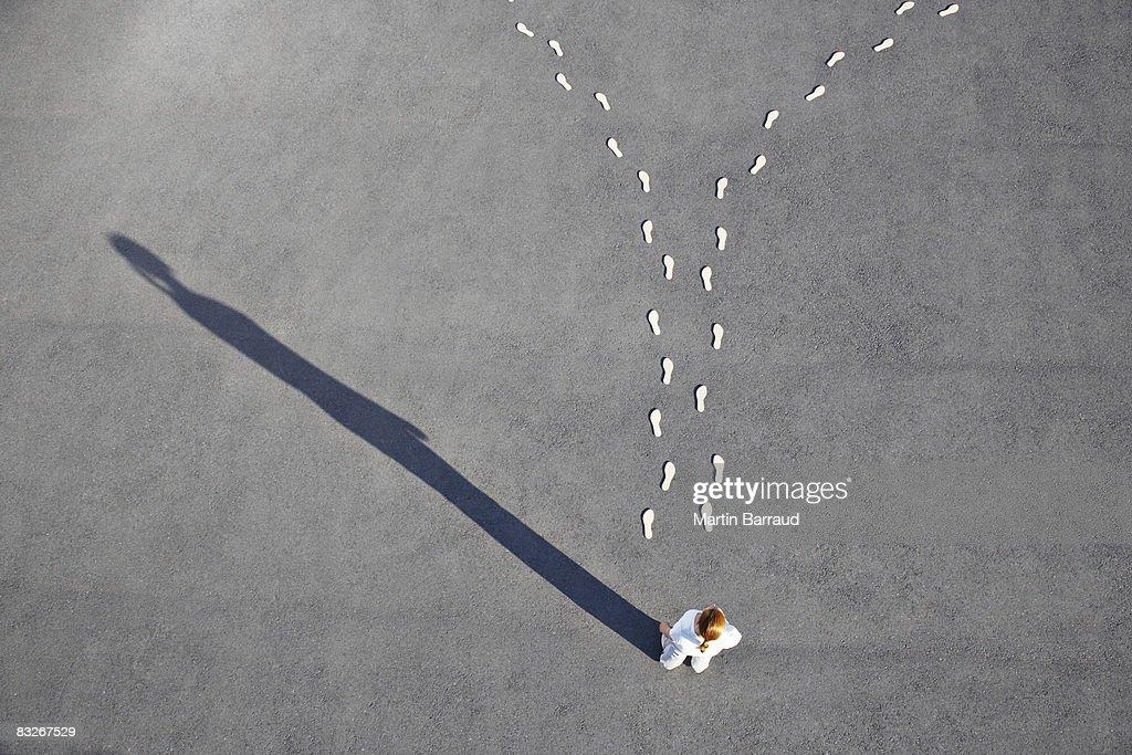 Woman looking at diverging footprints : Stock Photo