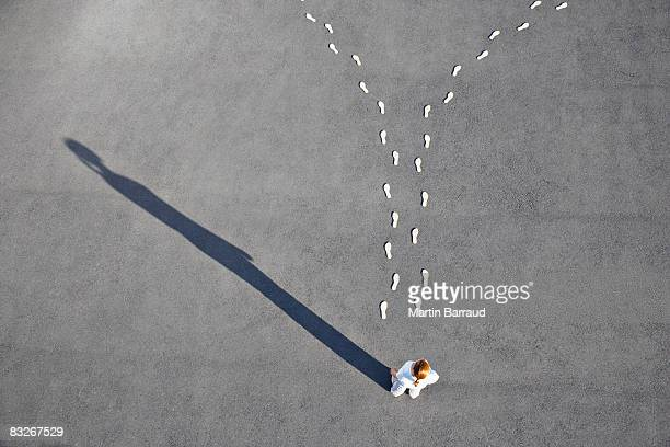 woman looking at diverging footprints - beslissingen stockfoto's en -beelden