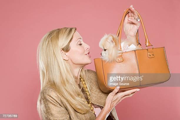Woman looking at dog in handbag