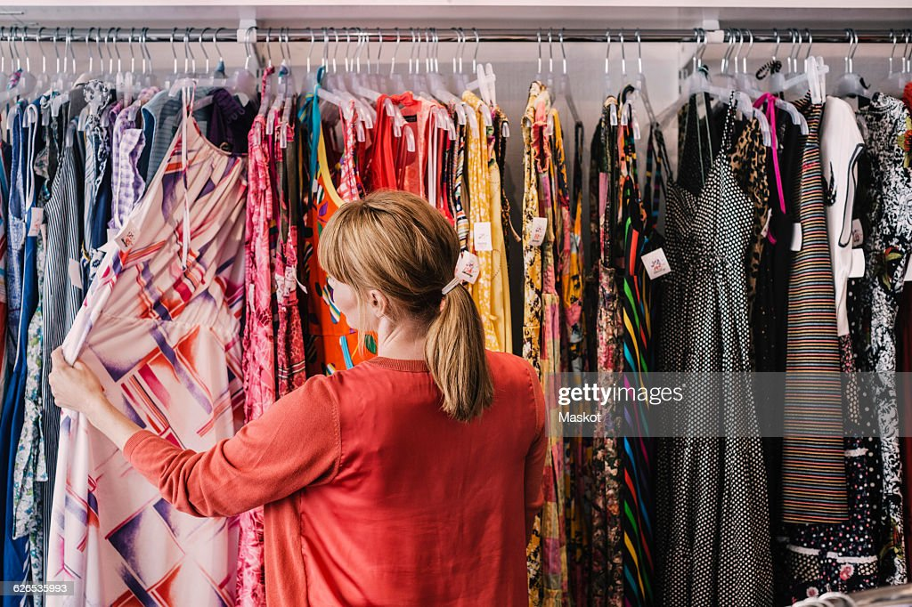 Woman looking at dress hanging on rack while standing at store : Stock Photo