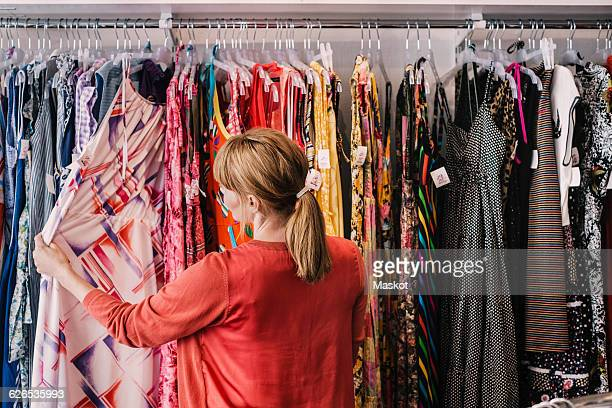 woman looking at dress hanging on rack while standing at store - kleding stockfoto's en -beelden