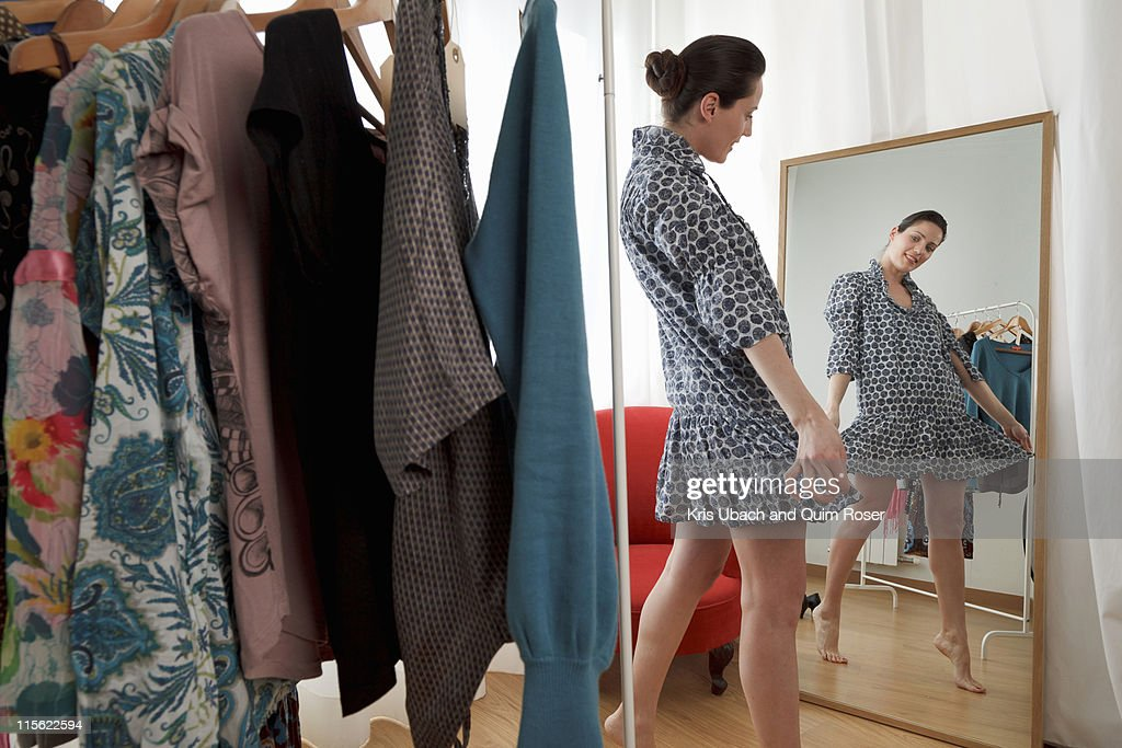 woman looking at dress in mirror : Stock Photo