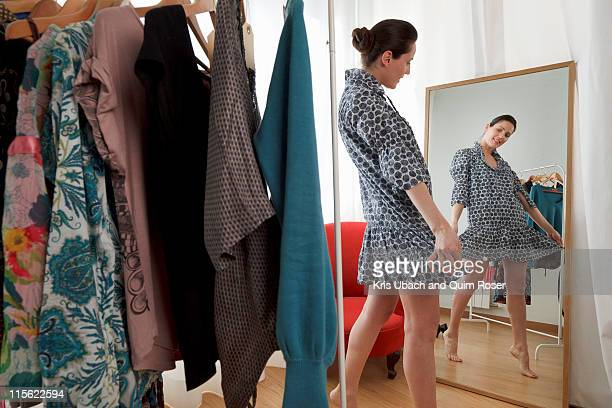 woman looking at dress in mirror - kleid stock-fotos und bilder