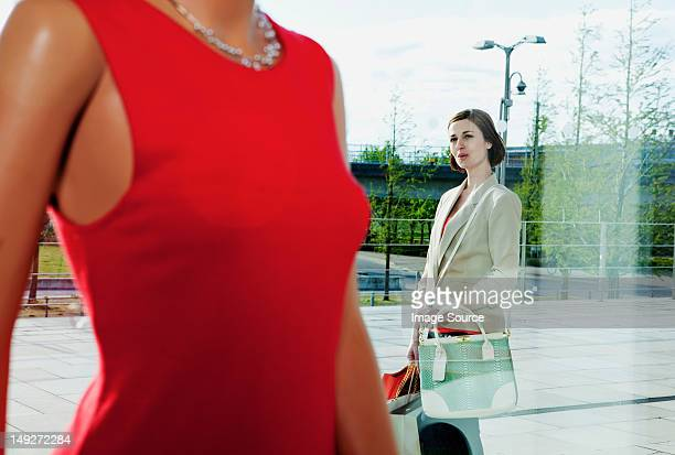 Woman looking at dress on mannequin in shop window