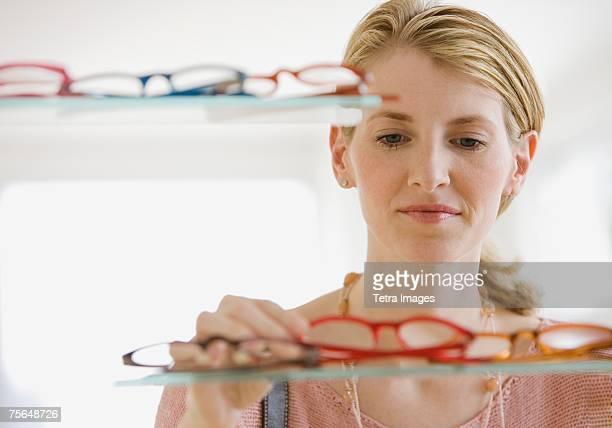 Woman looking at eyeglasses in store