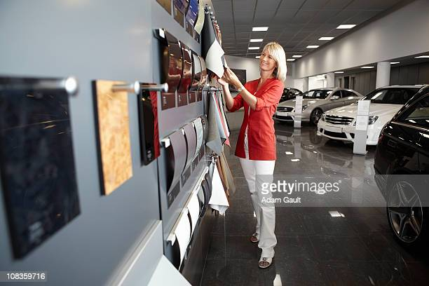 Woman looking at fabric samples in automobile showroom