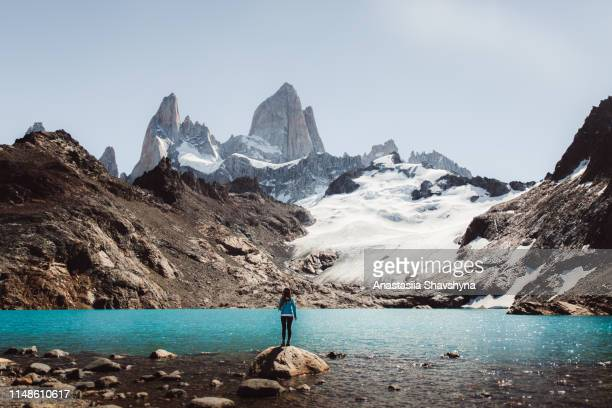 woman looking at fitz roy mountain and turquoise lagoon in el chalten, argentina - argentina stock pictures, royalty-free photos & images