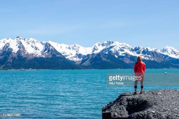 woman looking at fjord and mountain range. - golfo do alasca imagens e fotografias de stock