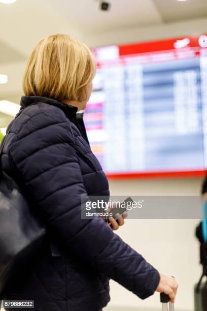 Woman looking at flight information screen in airport